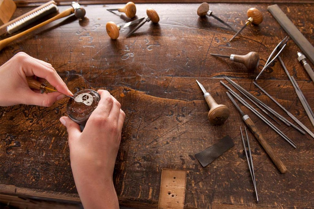 An Arnold & Son Craftsman at the beginning of crafting a timepiece