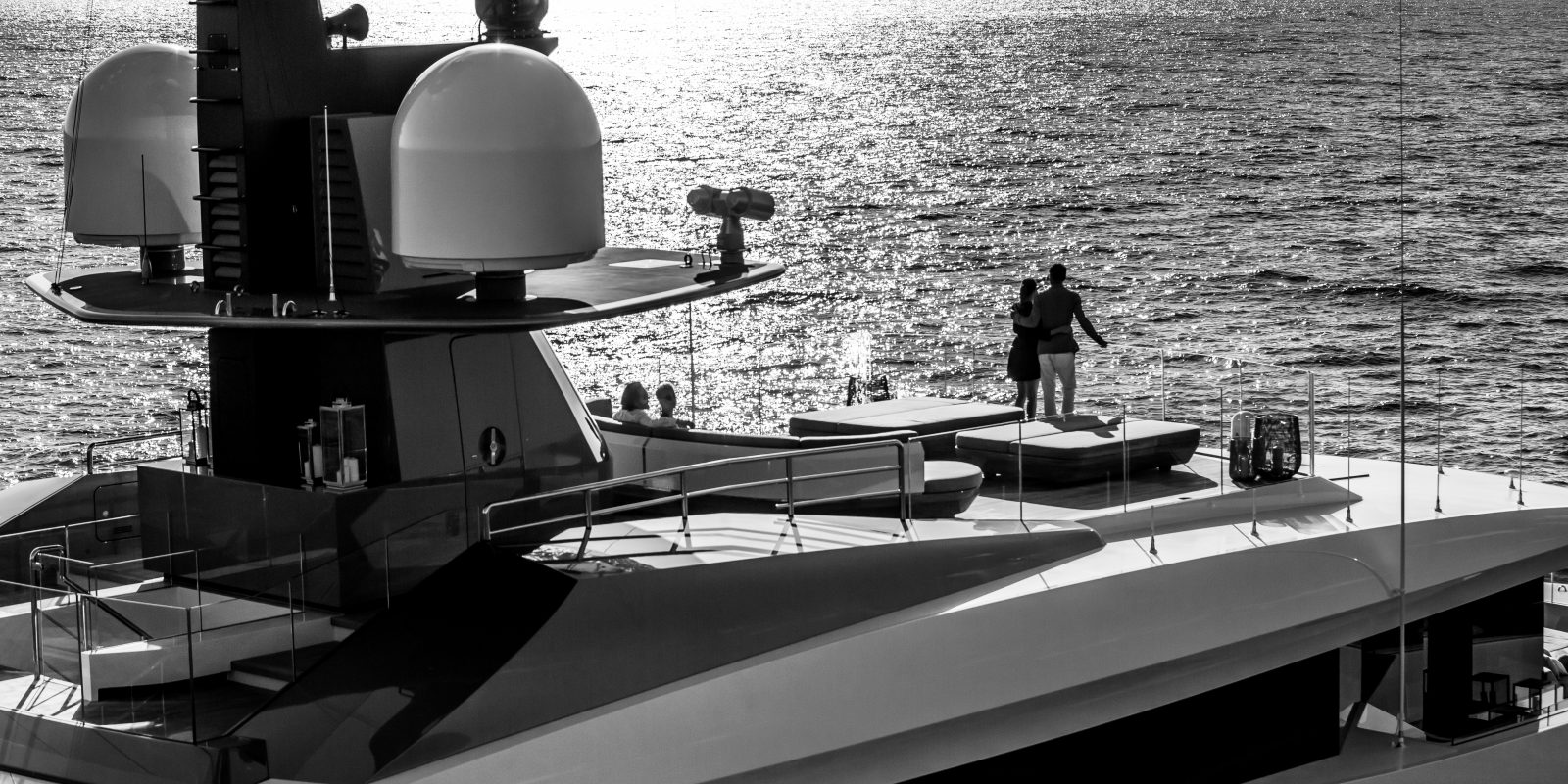 Black and white image of couple looking into the horizon on board yacht for sale