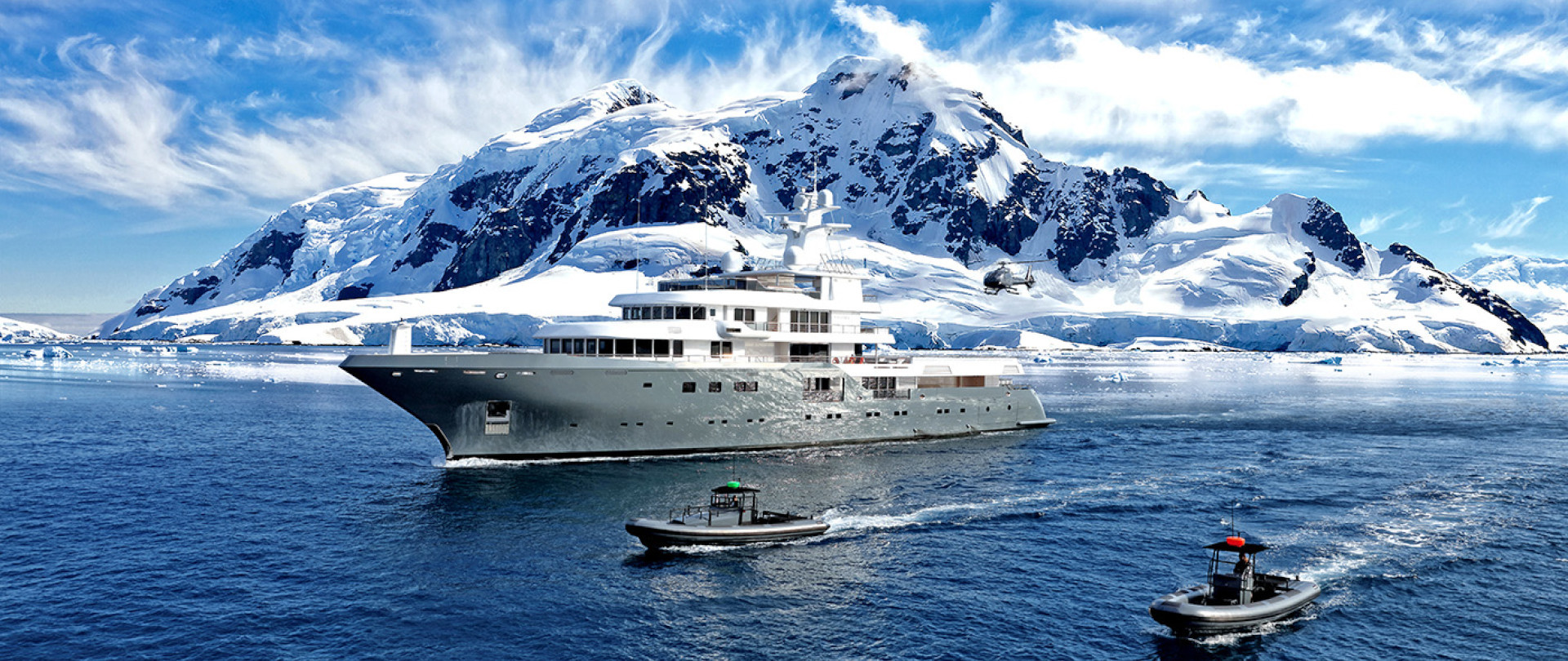 antarctica yacht charter with whales and ice bergs in the background