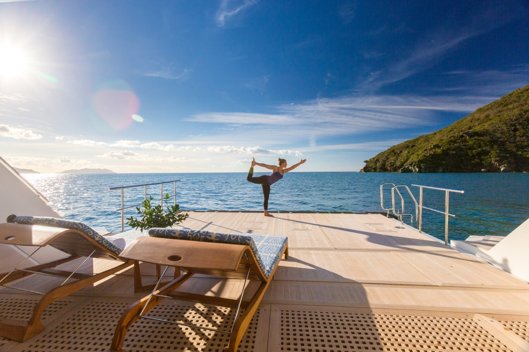 Icon Charter Yacht PARTY GIRL girl on beach club doing yoga in the Caribbean