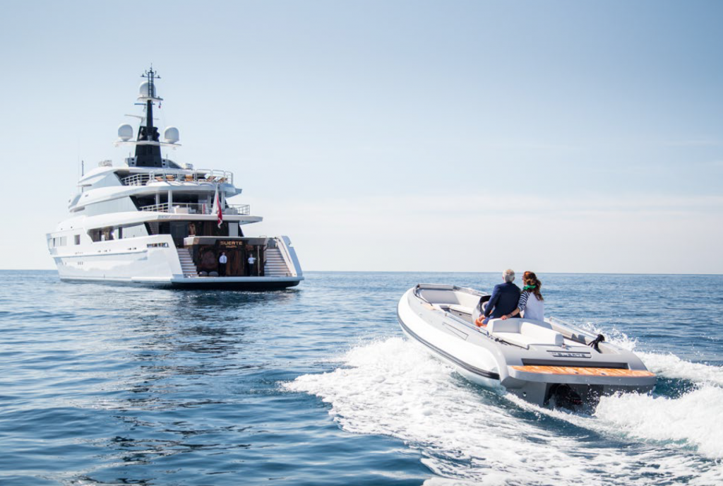 uhnw couple onboard luxury tender cruising to luxury superyacht at anchor in mediterranean sea