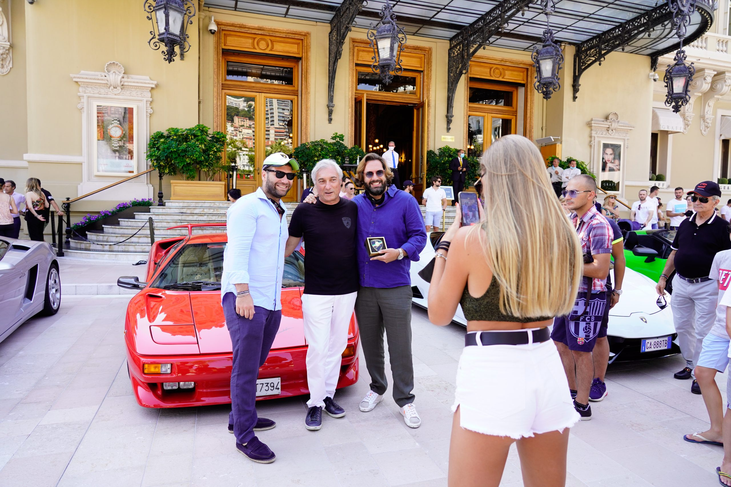People taking a photo in front of a Lamborghini